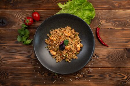 ebi chahan fried japanese rice with vegetables, shrimp and soy sauce in a black plate on a wooden background