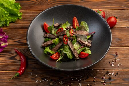 Thai beef salad of baked veal tenderloin, salad mix, cherry, chili pepper with olive oil in a black plate on a wooden background