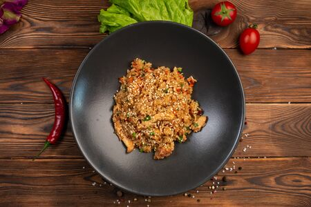 tori tyahan fried Japanese rice with vegetables and chicken in soy sauce in a black plate on a wooden background