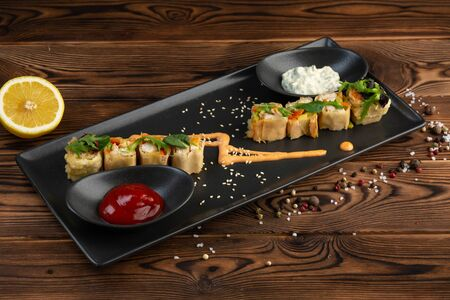 set of rolls in batter decorated with greens on a black rectangular plate with white and red sauce in cups