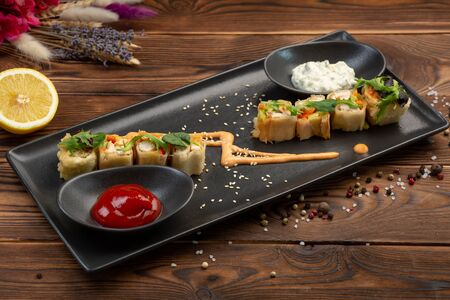 set rolls in batter decorated with greenery on a black rectangular plate