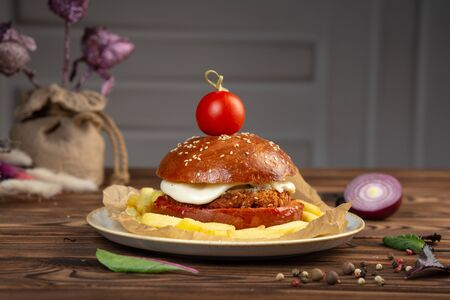 cheeseburger decorated with cherry tomato on a plate on a wooden table
