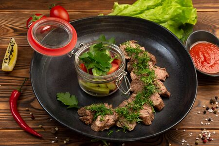 machete steak minced veal tenderloin steak with fresh salad and spicy sauce in a black plate on a wooden background Stock Photo