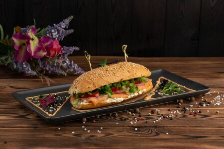 delicious baguette with salmon with salad and sesame seeds closeup on wooden board, black background. Banco de Imagens
