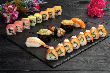 sushi roll set on black stone on dark wooden background 版權商用圖片