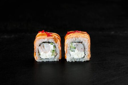 pair of sushi rolls close-up on a dark background