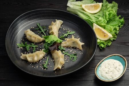 gedza syumai steamed chinese dumplings with shrimp and vegetables in a black plate nna on a dark background, served with sauce Banco de Imagens