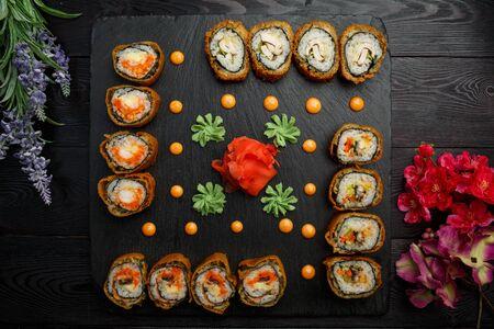 sushi rolls hotto set on black stone on dark wooden background Banco de Imagens