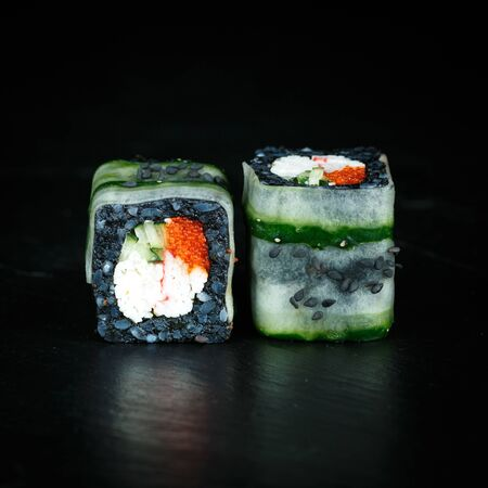 pair of sushi rolls black kani close-up on a dark background