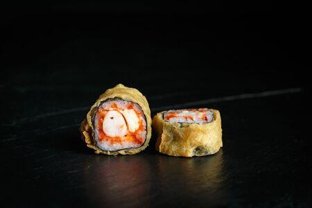pair of sushi rolls tempura ebi itame with krab close-up on a dark background