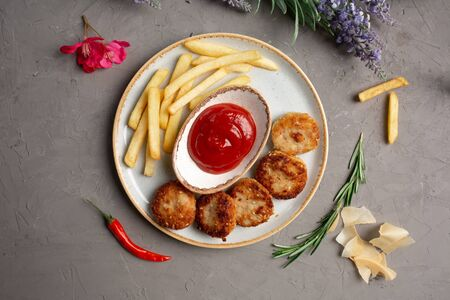 french fries, meat cutlets and ketchup in a white plate on a gray background