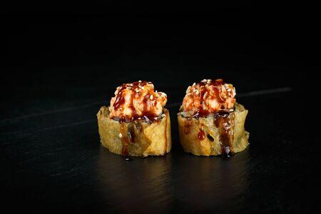 pair of sushi rolls segun close-up on a dark background
