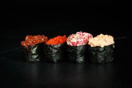 assorted gunkans with salmon, caviar, crab, avocado on a black background