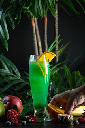 Curacao lemonade in a glass decorated with an orange slice: kiwi syrup, passion fruit puree, curacao syrup, fresh apple, orange, kiwi, sprite