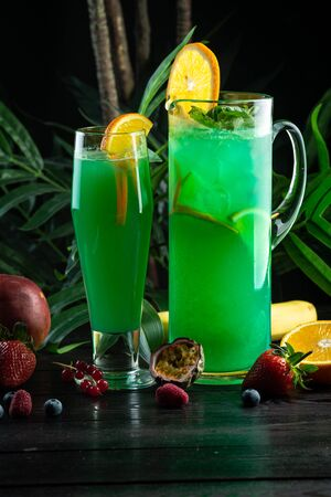 Curacao lemonade in a glass and jug decorated with an orange slice: kiwi syrup, passion fruit puree, curacao syrup, fresh apple, orange, kiwi, sprite 版權商用圖片
