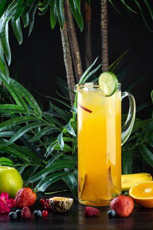 pineapple mango cocktail in a jug on a dark background with fruits: Pineapple, Mango, Strawberry, Mango Puree, Pineapple Juice, Peach, Apple, Sprite 版權商用圖片