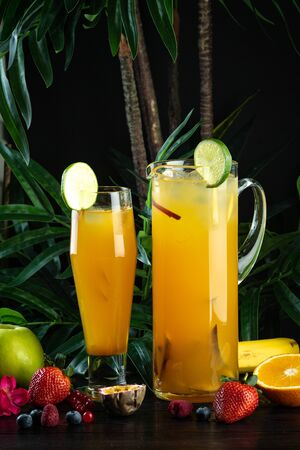 pineapple mango cocktail in a jug and glass on a dark background with fruits: Pineapple, Mango, Strawberry, Mango Puree, Pineapple Juice, Peach, Apple, Sprite