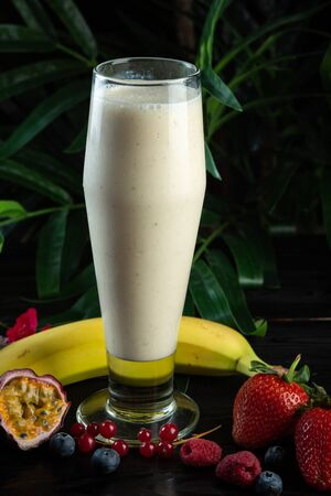 milkshake in a glass and fruits on a dark background