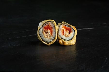 pair of sushi rolls imperator close-up on a dark background