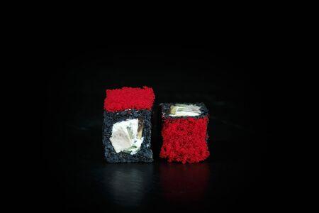 pair of sushi black chicken rolls close-up on a dark background