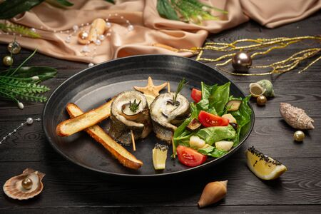 Baked seabass with eggplant, mozzarella cheese, with fresh salad and grissini sticks in a black plate on a dark wooden background