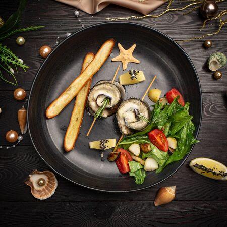 Branzino al forno con melanzane, mozzarella, con insalata fresca e bastoncini di grissini in un piatto nero su fondo di legno scuro
