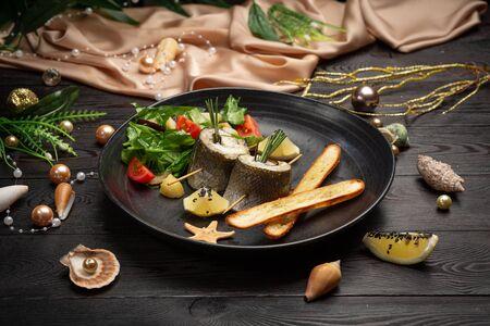 Branzino al forno con melanzane, mozzarella, con insalata fresca e bastoncini di grissini in un piatto nero su fondo di legno scuro Archivio Fotografico