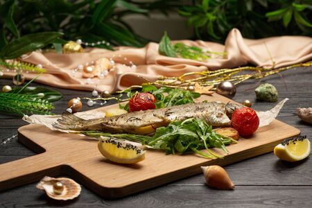 fried trout with arugula, cherry tomatoes and lemon on a board on a dark wooden background