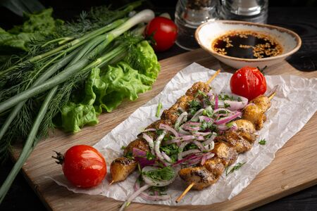 skewers of chicken on a skewer on the board on a dark background. chicken, red onion, cilantro, green onion, tomato