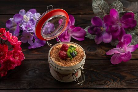 creamy dessert in a jar decorated with chocolate chips and berries on a dark wooden background 免版税图像