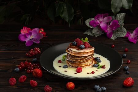 pancakes with condensed milk decorated with berries in a black plate on a dark wooden background 免版税图像