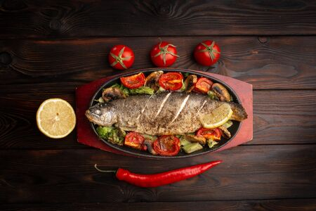 baked trout with vegetables on an oval plate decorated with fresh tomatoes and chili peppers on a dark wooden background