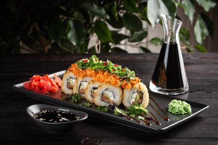 sushi roll set on a round plate and soy sauce on a dark wooden background 免版税图像