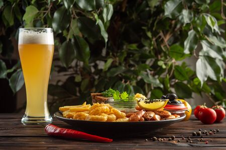 glass of foamy beer and a plate with snacks: shrimp, squid rings, french fries, rye croutons, olives on a wooden background