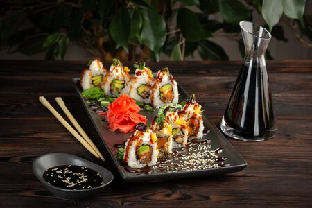 set of sushi rolls on a rectangular black plate with soy sauce and chopsticks on a black wooden background