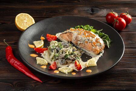 salmon steak in white sauce with red caviar and vegetable stew in a round plate on a dark wooden background 免版税图像