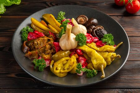 salted and pickled vegetables: on a black plate on a wooden background