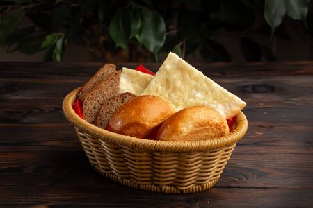 assorted bread in a basket on a dark wooden background