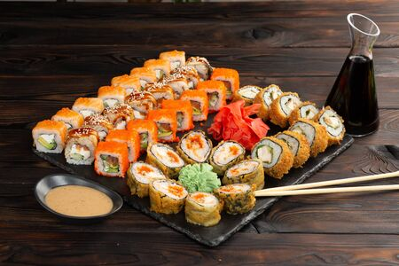 sushi set with sauce and chopsticks on a black board on a dark wooden background