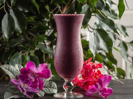 Cocktail with fruits and berries in a tall glass on a dark wooden background