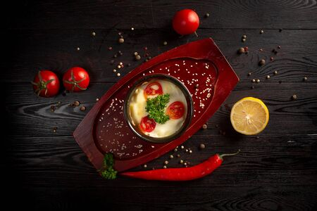 mashed potato in a pot decorated with tomatoes and parsley on a dark wooden background