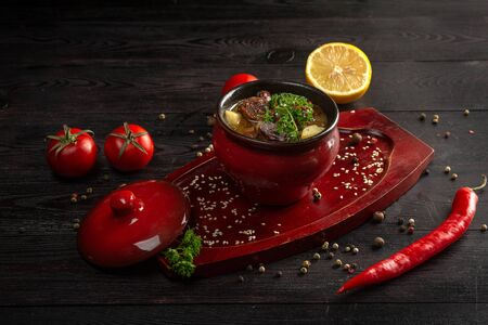 vegetable stew with potatoes and meat in a pot decorated with parsley on a dark wooden background 免版税图像