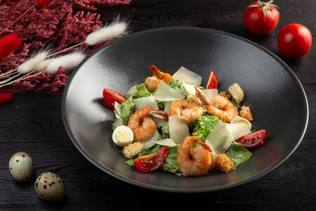 caesar salad with shrimp in a black plate on a dark wooden background