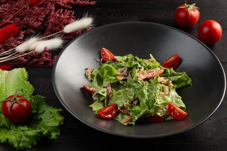 salad with tomatoes and leafy greens in a black plate on a dark wooden background 免版税图像