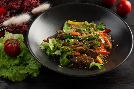 funchose noodles with veal in a black plate on a dark wooden background
