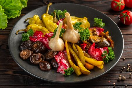 salted and pickled vegetables: cucumbers, garlic, pepper, mushrooms, cabbage, eggplanton a black plate on a wooden background 免版税图像