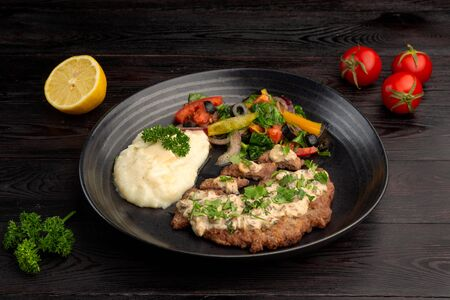 fried steak and mashed potatoes with fresh vegetables salad on a round plate on a dark wooden background 免版税图像