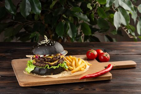 blackburger black mamba with marbled beef with french fries, chili pepper and tomatoes on a wooden board on a wooden table 免版税图像