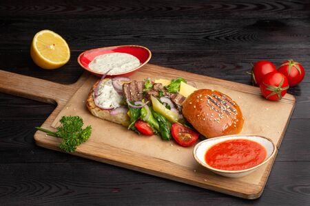 fried steak, fresh vegetables, greens and bread on a wooden board on a dark wooden background 免版税图像
