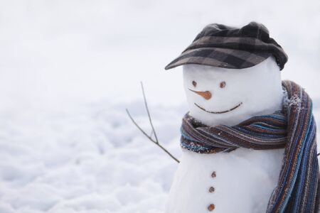 peaked: Snowman in brown peaked cap and scarf Stock Photo